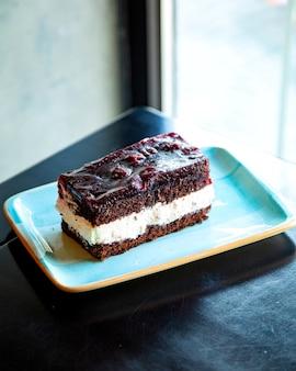 Stück schokoladenkuchen mit sahne auf einem blauen teller