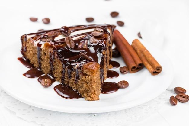Stück schokoladenkuchen mit schokoladensirup beträufelt