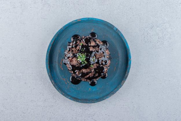 Stück schokoladenkuchen mit sirup auf blauem teller dekoriert. foto in hoher qualität
