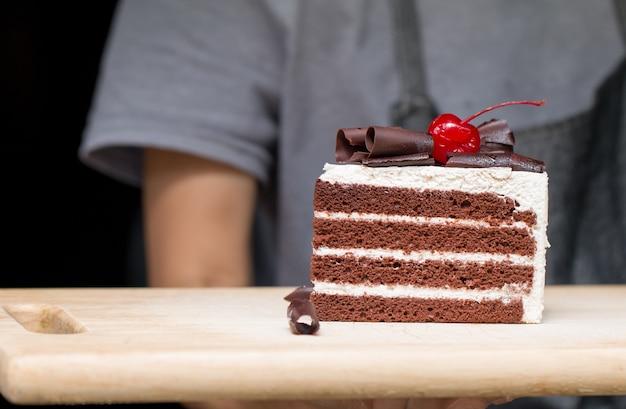 Stück schokoladenkuchen mit vanille zuckerguss und kirschgelee.
