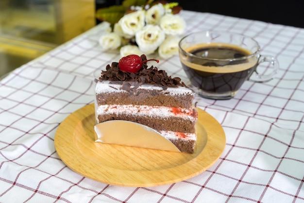 Stück schwarzwaldkuchen auf hölzerner platte und kaffeetasse