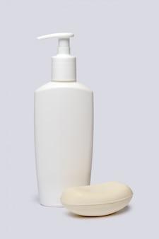 Stück seife und flasche flüssigseife über hellgrauem hintergrund mit beschneidungspfad