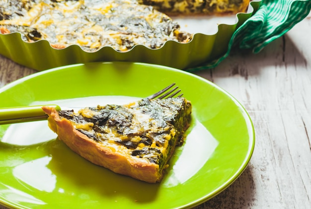 Stück spinat-tarte auf grünem teller