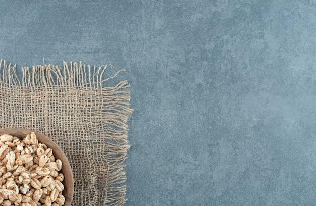 Stück stoff unter einer kleinen holzschale gefüllt mit flocken auf marmorhintergrund. foto in hoher qualität
