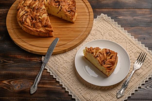 Stück traditioneller hausgemachter cornish pie auf einem teller auf leinenserviette mit messer und gabel