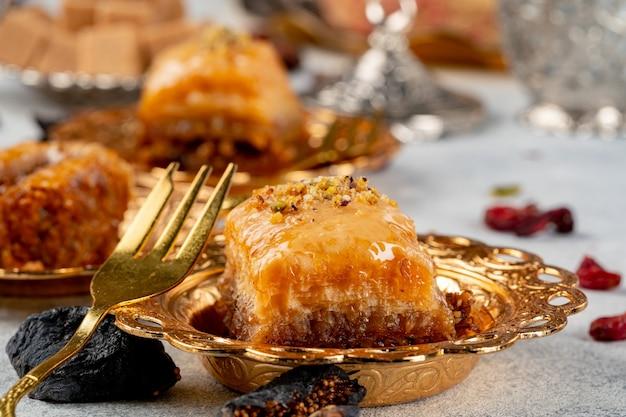 Stück türkisches baklava in goldener arabischer platte
