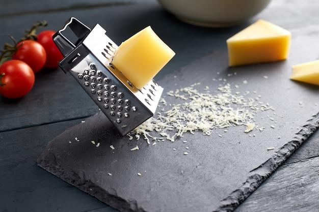 Stück und geriebener parmesankäse auf schwarzem servierbrett auf holztisch