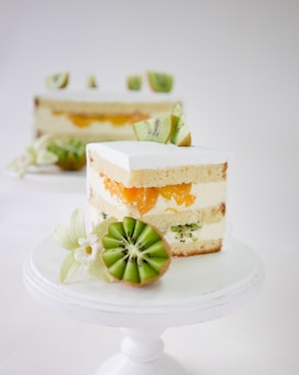 Stück vanillekuchen mit frischer kiwi und pfirsichen auf weißem hölzernem kuchenstand