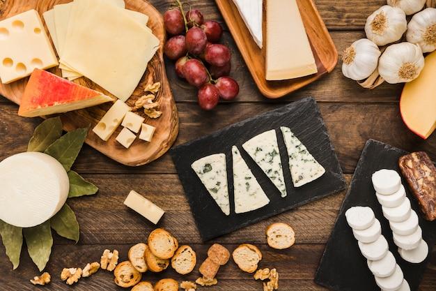 Stück verschiedene käsesorten mit trauben; brotscheibe; walnuss und knoblauch auf dem schreibtisch
