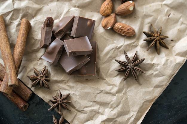 Stück vollmilchschokolade mit ganzem mandel-zimt-flatlay