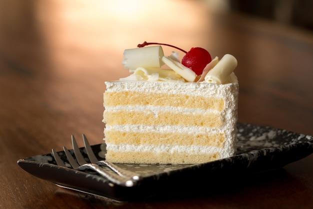 Stück weißer kuchen mit dem vanilleüberfrieren und kirschgelee, überstiegen mit weißem käse