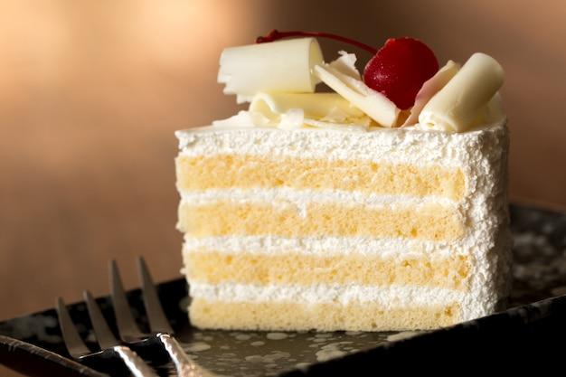 Stück weißer kuchen mit vanillezucker und kirschgelee, belegt mit weißem käse