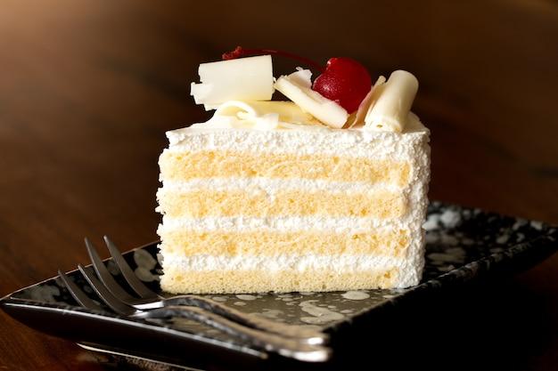 Stück weißer kuchen mit vanillezucker und kirschmarmelade, belegt mit weißem käse