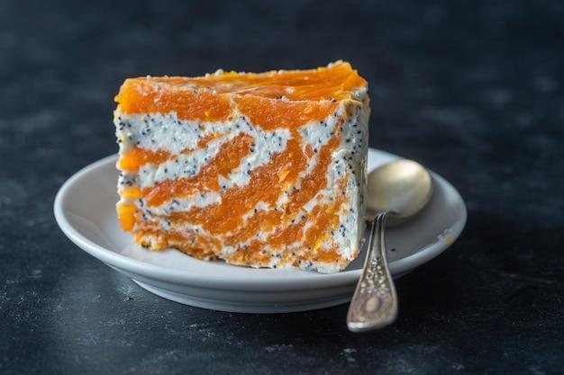 Stück zarter karottenquarkkuchen mit mohn, honig und orangensaft im teller, nahaufnahme. kuchen ohne backen