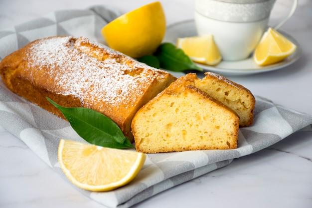 Stück zitronenkuchen auf küchentuch mit zitronen und teetasse. einfaches rezept von zitrusdessert für das tägliche kochen.