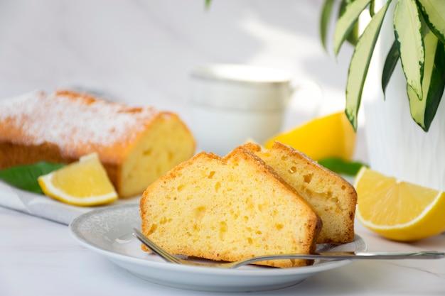 Stück zitronenkuchen auf teller auf marmortisch und grüner pflanze im blumentopf mit vollem kuchen und zitronen auf hintergrund. hausgemachte bäckerei nach klassischem rezept. leckeres dessert zum frühstück teezeit.