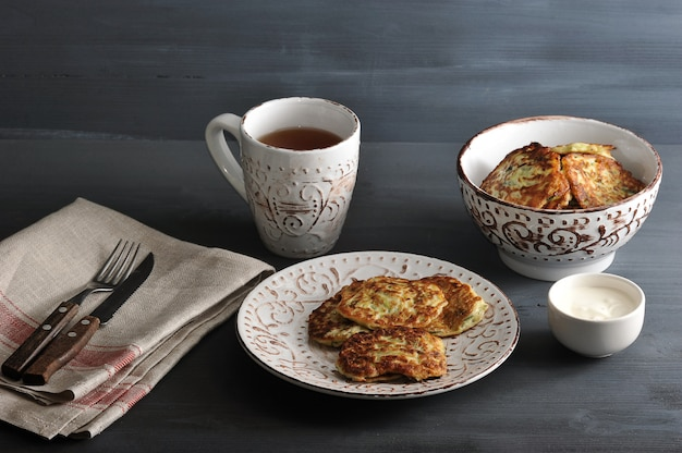 Stückchen der zucchini mit tee auf rustikalem