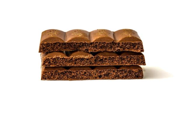 Stückchen kohlensäurehaltiger schokolade auf weiß