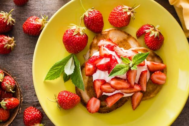 Stückchen mit joghurt, geschnittenen erdbeeren und tadellosen blättern auf einer platte. ansicht von oben