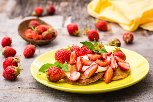 Stückchen mit joghurt, geschnittenen erdbeeren und tadellosen blättern auf einer platte