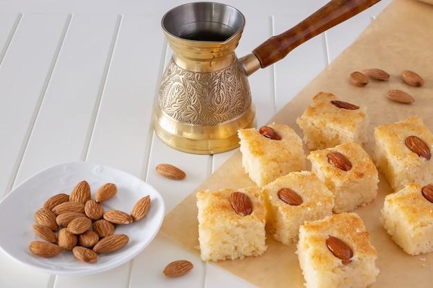 Stücke basbousa oder namoora traditionelles arabisches süßes dessert mit mandeln. hausgemachter grießkuchen. leerzeichen kopieren. selektiver fokus. horizontal.