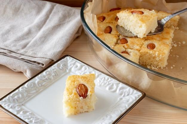 Stücke basbousa oder namoora traditionelles arabisches süßes dessert mit mandeln. hausgemachter grießkuchen. selektiver fokus.