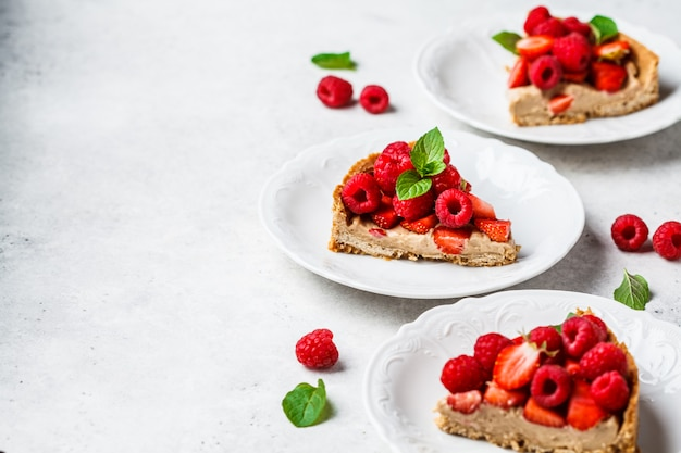 Stücke beerentörtchen mit himbeeren, erdbeeren und sahne auf weißen platten