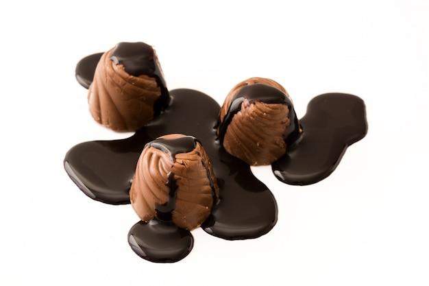 Stücke bonbons bedeckt mit der geschmolzenen schokolade lokalisiert auf weißem hintergrund
