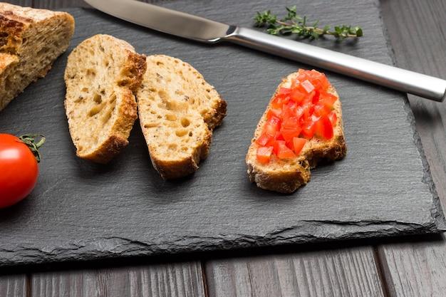 Stücke brot und messer. in scheiben geschnittenes tomatensandwich. leckerer snack und vorspeise. draufsicht