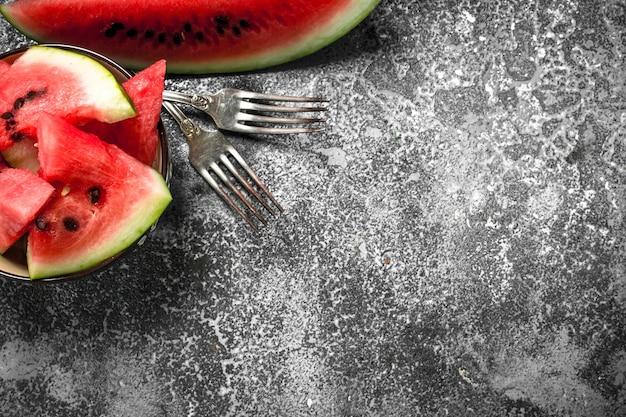 Stücke der frischen wassermelone in einer schüssel auf rustikalem tisch.