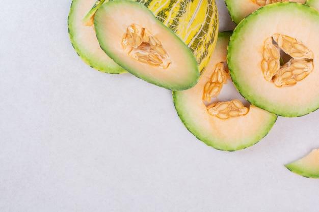 Stücke der grünen melone auf weißer oberfläche