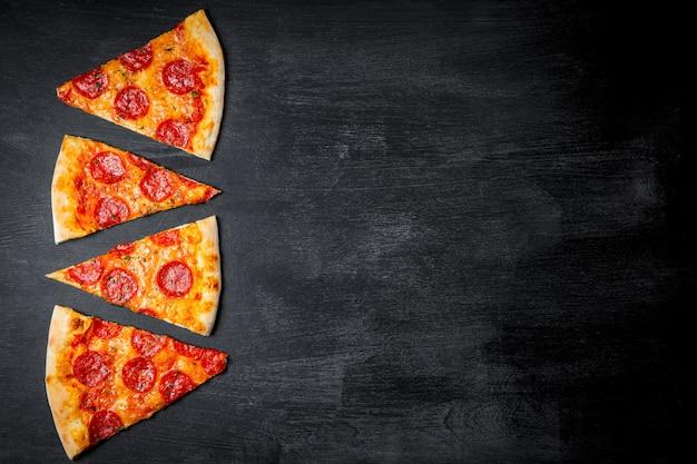 Stücke der klassischen italienischen peperoni-pizza auf schwarzem hintergrund, draufsicht. hochwertiges foto