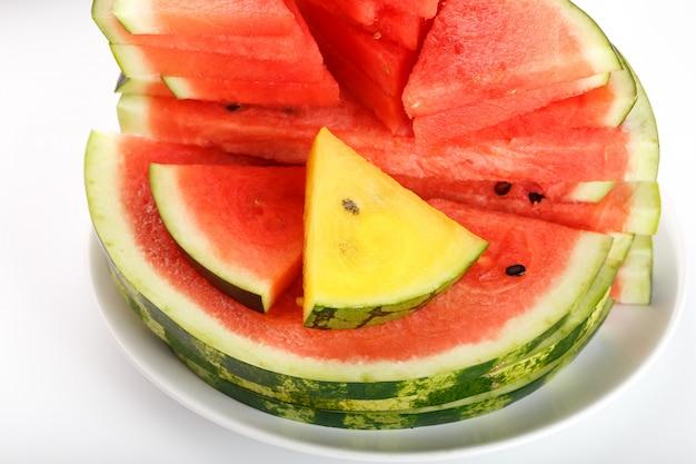 Stücke der roten und gelben wassermelone in einer weißen runden platte