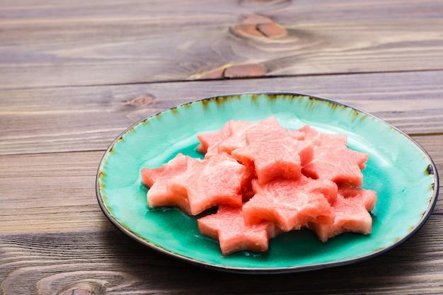 Stücke der wassermelone in form von sternen auf einer keramischen platte auf woodtable