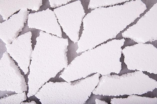 Stücke der weißen expandierten polystyrol-nahaufnahme auf einem grauen hintergrund, flaches layout.