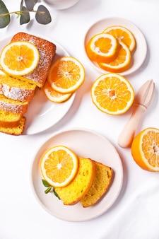 Stücke des frischen hausgemachten gebackenen geschnittenen zitronenkuchens auf dem weißen teller. draufsicht.