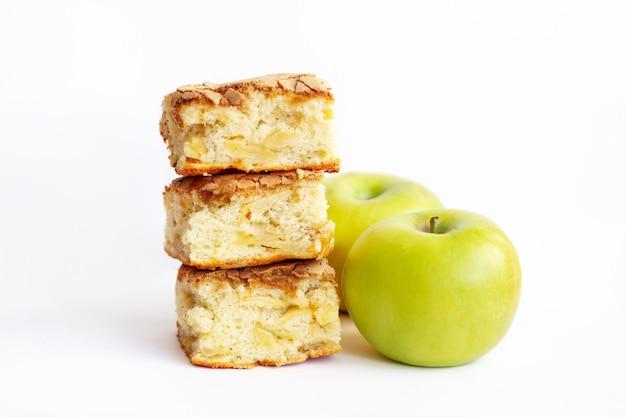 Stücke des hausgemachten organischen schwammapfelkuchens nahe grünen äpfeln lokalisiert auf einem weißen hintergrund. nahaufnahme eines desserts charlotte