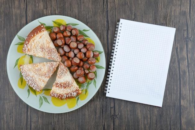 Stücke des köstlichen kuchens mit macadamia-nüssen, die auf einem hölzernen hintergrund gelegt werden.