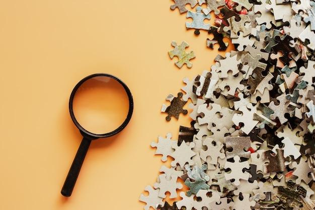Stücke des puzzlen mit lupe auf beige farbhintergrund