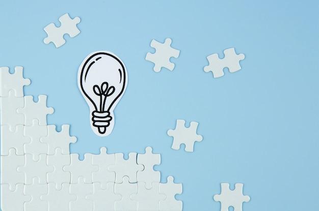 Stücke des puzzlespiels mit glühlampe auf blauem hintergrund