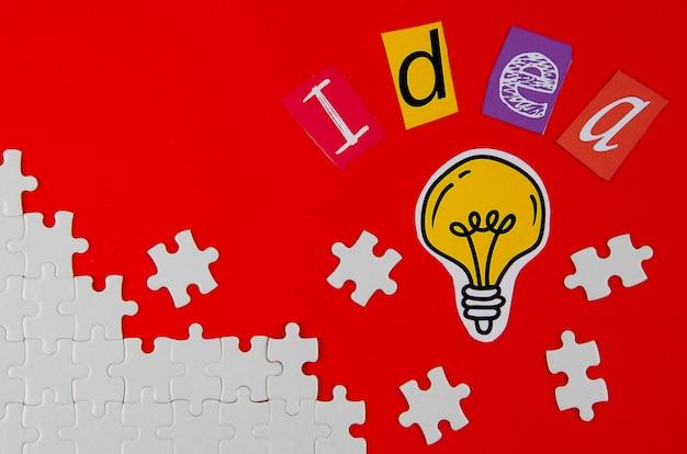 Stücke des puzzlespiels mit glühlampe auf rotem hintergrund