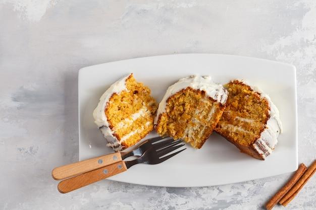 Stücke des veganen hausgemachten karottenkuchens mit weißer sahne auf einem weißen teller, draufsicht. festliches dessertkonzept.