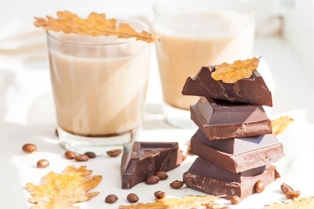 Stücke dunkler schokolade, kaffeebohnen und tassen kakao oder kaffee mit milch auf weißem tisch. herbstkonzept. sonniger tag, gelbe trockene blätter.