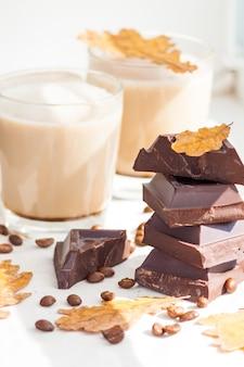Stücke dunkler schokolade, kaffeebohnen und tassen kakao oder kaffee mit milch