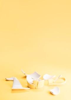 Stücke eines defekten gelben bechers