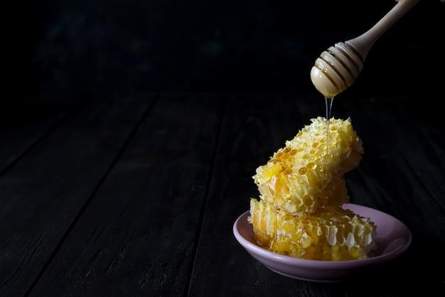 Stücke frische bienenwabe mit einem hölzernen schöpflöffel, der honig auf einer keramischen platte tropft