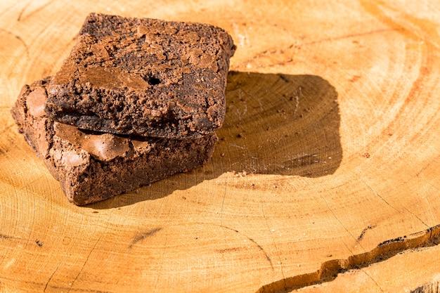 Stücke frischer brownie auf hölzernem hintergrund. leckerer schokoladenkuchen. makro-nahaufnahme. selektiver fokus.