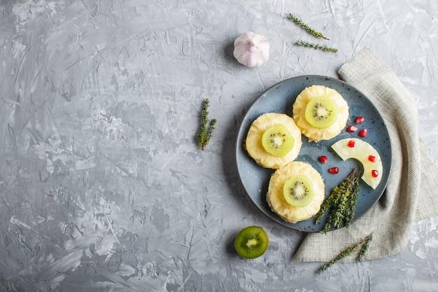 Stücke gebackenes schweinefleisch mit ananas, käse und kiwi auf grauem hintergrund.