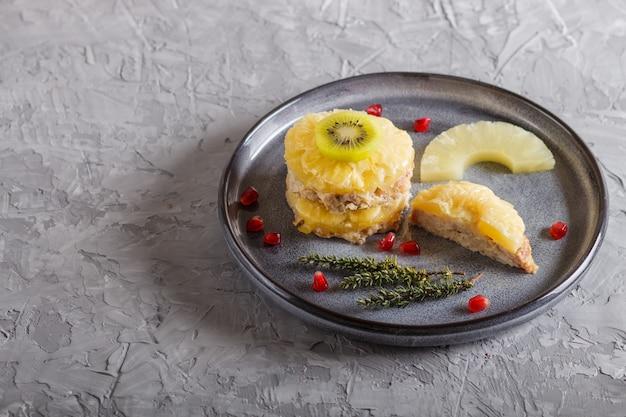 Stücke gebackenes schweinefleisch mit ananas, käse und kiwi auf grauer platte.