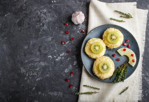 Stücke gebackenes schweinefleisch mit ananas, käse und kiwi auf schwarzem hintergrund.
